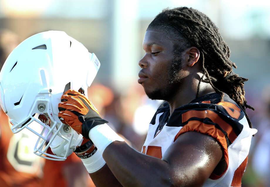 Malik Jefferson puts his helmet back on after a break as the Texas Longhorns conduct their first football practice on Aug. 7, 2015. Photo: Tom Reel /San Antonio Express-News