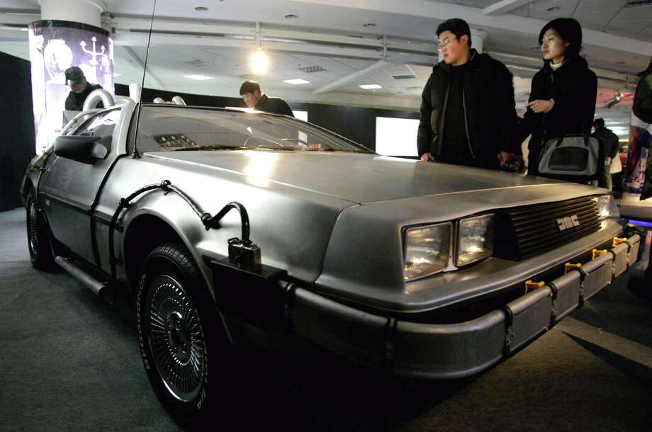 "Visitors at a 2005 car show in China look at the DeLorean used in the 1985 movie ""Back to the Future."" Photo: Eugene Hoshiko /Associated Press / AP"