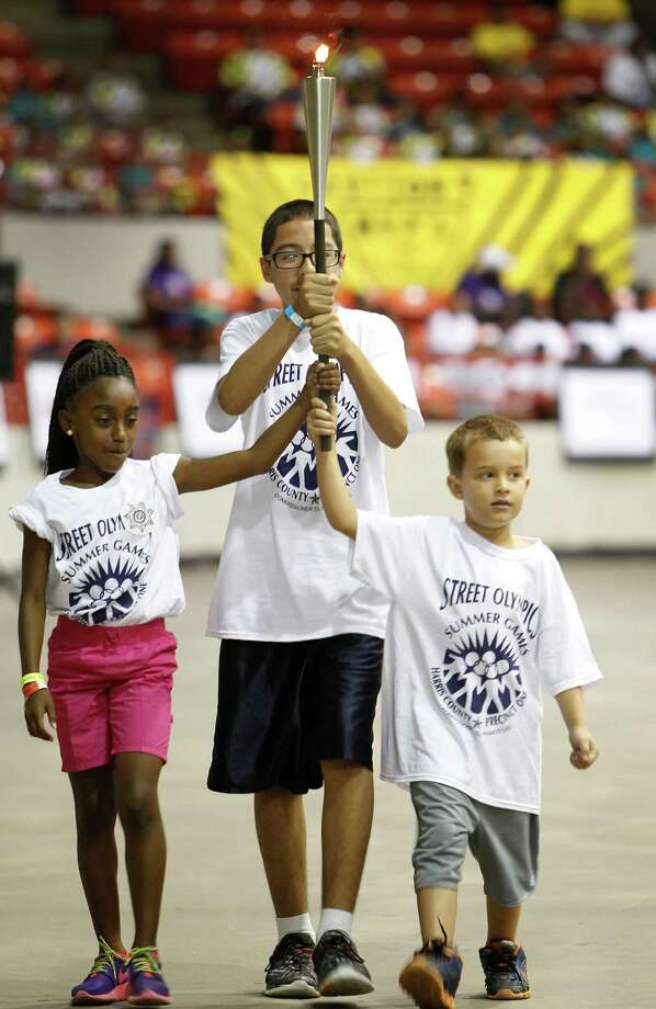 Kaelyn Small, 9, left, Daniel Torrez, 13, and Timothy Giddens, 6, carried in the Olympic flame for the 29th Annual Harris County Precinct One Street Olympics' Summer Games Friday, Aug. 7, 2015, in Houston.  About 2,500 boys and girls ages 6 to 15 will compete for 300 gold, silver and bronze medals awarded in each of the 12 sports and in each age division. The competitions range from basketball agility and sprints to Hula Hoop, hopscotch and jacks. These children are the best of approximately 3,500 participants who practiced and competed for 8 weeks at 45 participating youth organizations in this free summer event. Photo: Steve Gonzales, Houston Chronicle / © 2015 Houston Chronicle