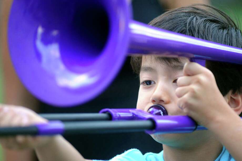 Taichi Henry, 8, of Nagoya Japan gets good sound from a trombone before the show with cellist Yo-Yo Ma and the Philadelphia Orchestra on Friday, Aug. 7, 2015, at Saratoga Performing Arts Center in Saratoga Springs, N.Y. (Cindy Schultz / Times Union) Photo: Cindy Schultz / 10032922A