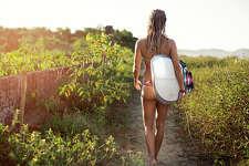 Female surfer wearing a bikini walks along a path