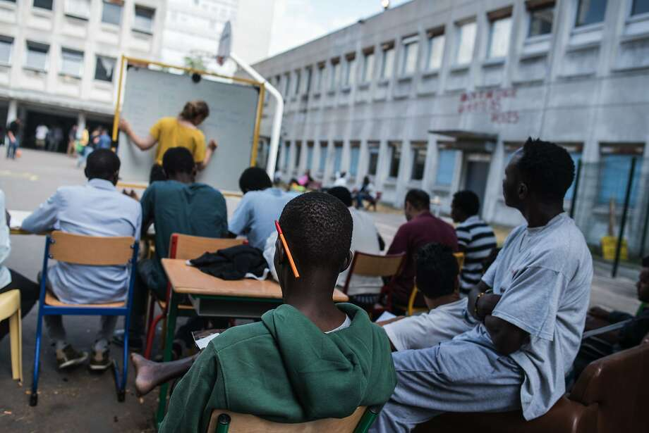 Camille Arrignon (in yellow) gives a French lesson to migrants who are staying on the grounds of the Guillaume-Bude secondary school building in Paris. About 200 migrants are living there. Photo: Kamil Zihnioglu, Associated Press