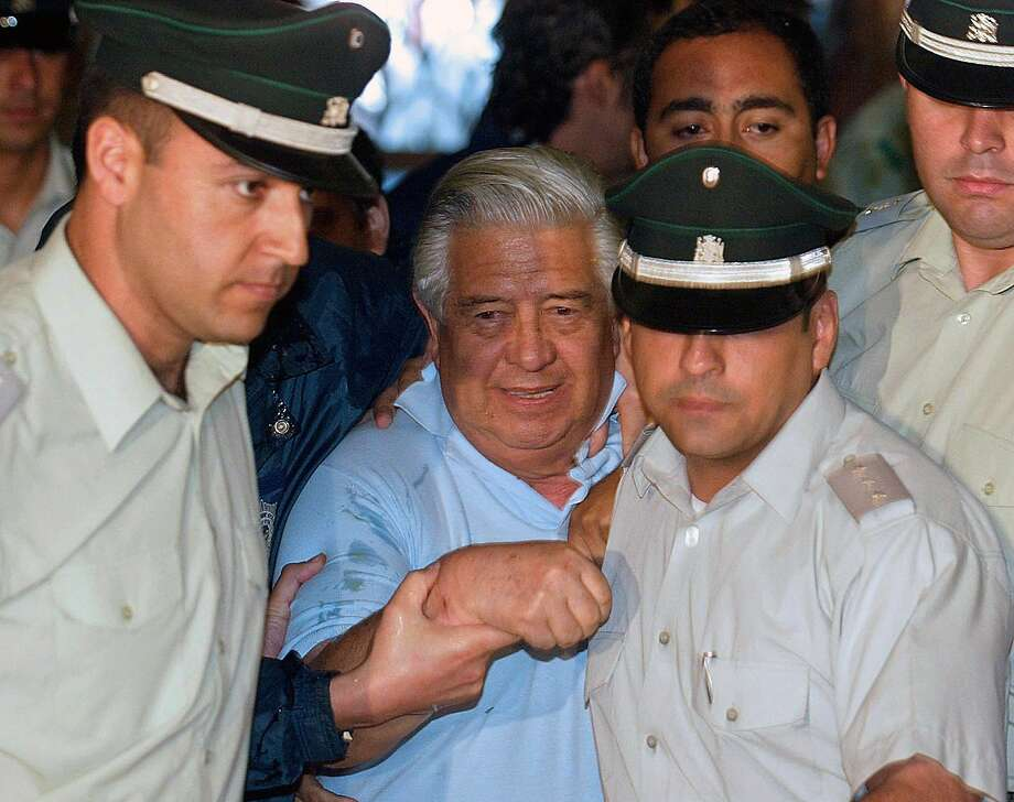 Gen. Manuel Contreras (center) was protected by guards at a court appearance in 2005. Photo: Martin Bernetti, AFP / Getty Images