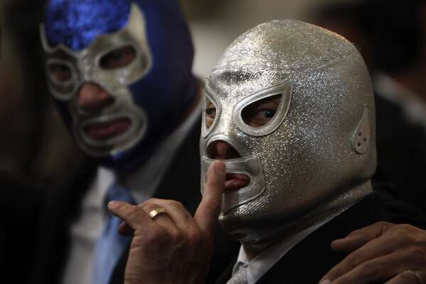Lucha libre icon   Mexican wrestler Hijo del Santo, right, motions towards a crowd as he stands with wrestler Blue Demon during a Mass in honor of the 25th anniversary of his father's death, Mexican legendary wrestler El Santo at the Metropolitan Cathedral in Mexico City, Thursday, Feb. 5, 2009.