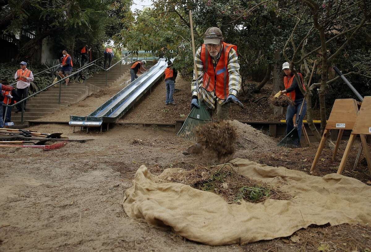 Neighbor, Eric Zigas collects debri as dozens of volunteers and neighbors join the San Francisco Public Works August Community Clean Team in the restoration of the Esmeralda Slide Park Plaza in San Francisco, Calif., on Sat. August 8, 2015.