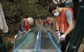 Nearby residents, Michal Kirchberger, (left) and J.T. Trollman sand the giant slide to prepare for painting as dozens of volunteers and neighbors join the San Francisco Public Works August Community Clean Team in the restoration of the Esmeralda Slide Park Plaza in San Francisco, Calif., on Sat. August 8, 2015.