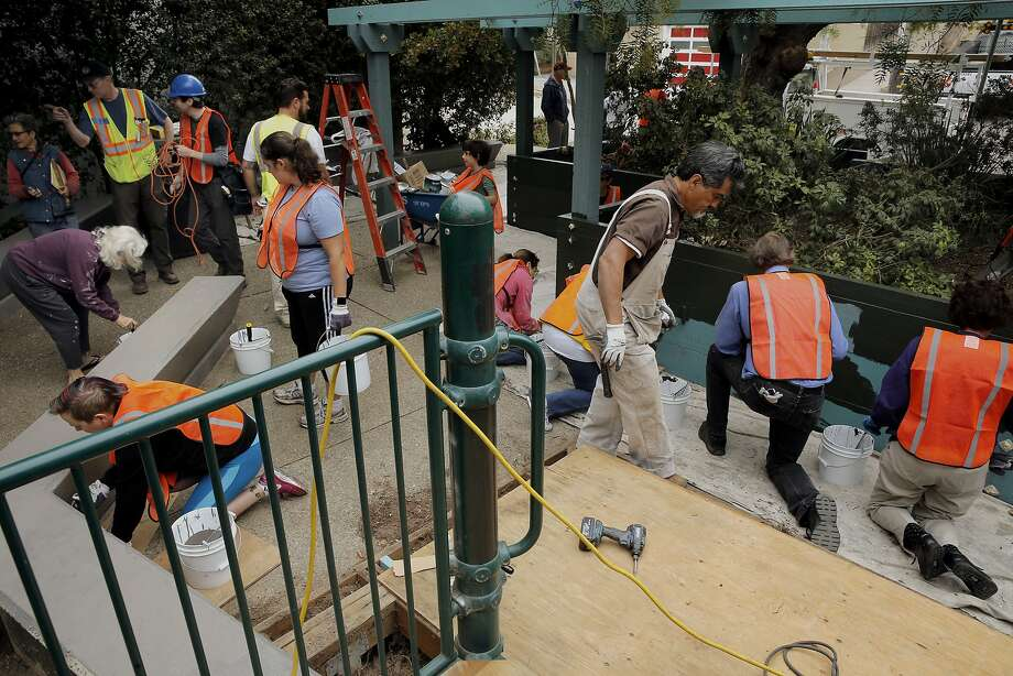 Volunteers and neighbors join workers from the San Francisco Public Works Department to restore the Esmeralda Street park plaza in San Francisco. Photo: Michael Macor, The Chronicle