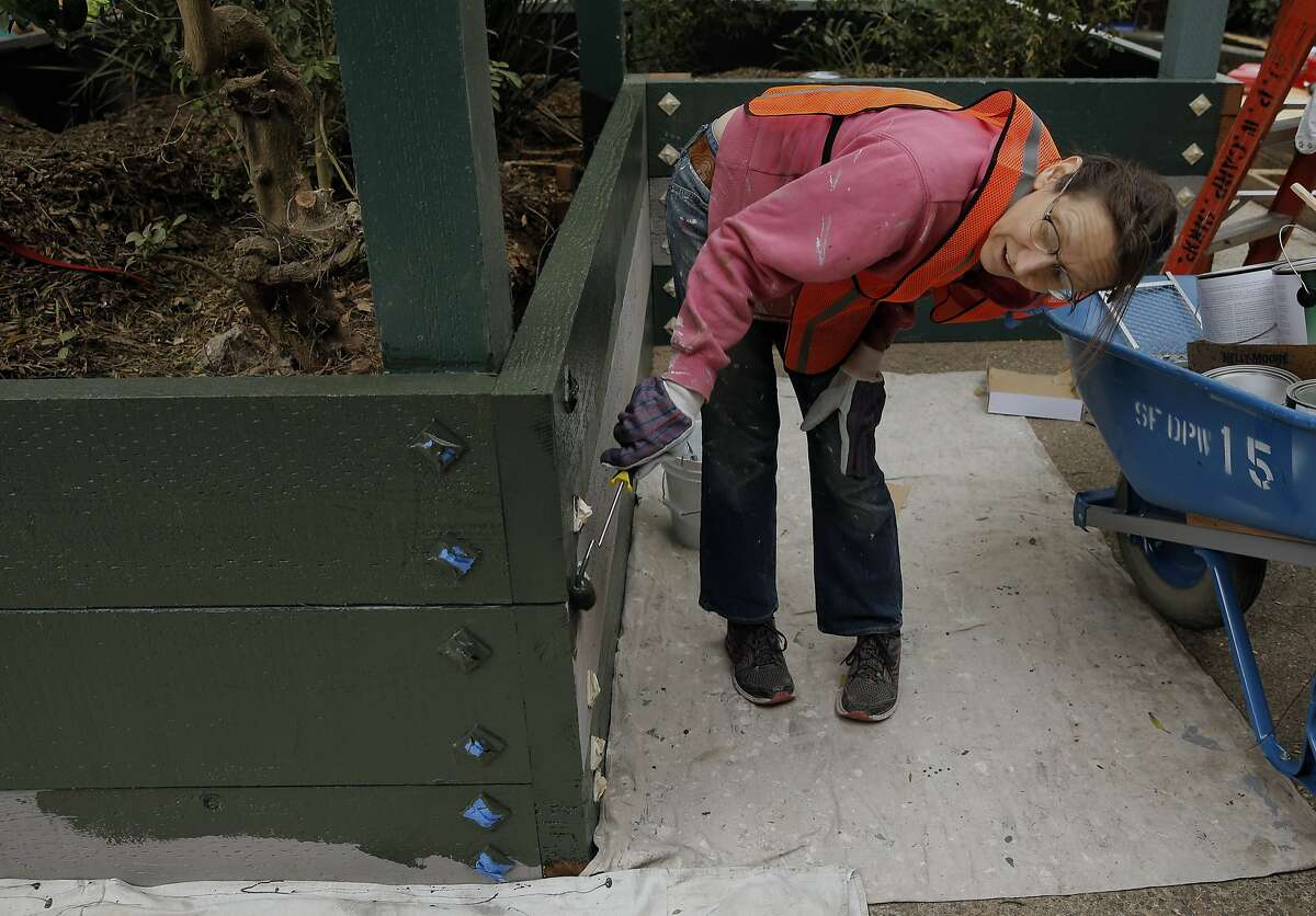 Neighbor, Becky Jennings paints a newly constructed planter box, as she joins dozens of volunteers, neighbors and the San Francisco Public Works August Community Clean Team in the restoration of the Esmeralda Slide Park Plaza in San Francisco, Calif., on Sat. August 8, 2015.