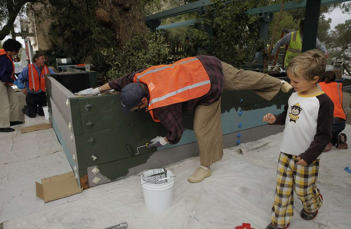 Neighbor Elaine Elinson paints a newly constructed planter box as she joins dozens of volunteers, neighbors and the San Francisco Public Works August Community Clean Team in the restoration of the Esmeralda Slide Park Plaza in San Francisco, Calif., on Sat. August 8, 2015.