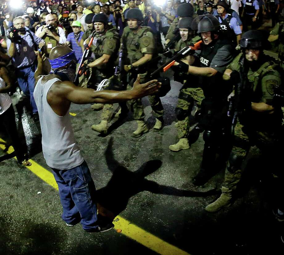 """FILE - In this Aug. 20, 2014 file photo, police arrest a man as they disperse a protest in Ferguson, Mo. The one year anniversary of the shooting of Michael Brown, which sparked months of nationwide protests and launched the """"Black Lives Matter"""" movement, is on Sunday, Aug. 9, 2015. (AP Photo/Charlie Riedel, File) ORG XMIT: TXBS208 Photo: Charlie Riedel / AP"""