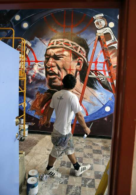 Teodoro Saavedra, (pictured) is working with Sarah Siskin to create a mural showing the Mapuche people an indigenous tribe of Chile, covering a wall at the La Pena Cultural Center in Berkeley, Calif., on Sat. August 8, 2015. La Pena is marking 40 years this year, a miracle when you consider that it is often struggling for money and that it has remained a singular mix of community, politics and the arts, with a view toward offering opportunities for a variety of communities, including undocumented immigrants. Photo: Michael Macor, The Chronicle