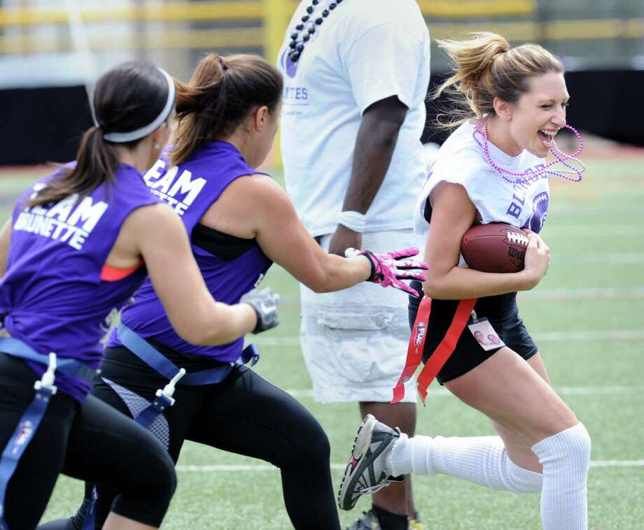At right, Blonde team running back Michelle Mastellone of Stamford breaks to the outside while being pursued by the Brunette team defense during the Alzheimer's Association Blondes vs. Brunettes flag football game at the Stamford High School football field in Stamford, Conn., Saturday, Aug. 8, 2015. Cate Burzynski of Stamford, one of the organizers of the event, said her grandfather, Richard Baca, recently passed away from Alzheimer's disease and that she was playing the game in his memory. Burzynski also said that $3,000 was raised from the charity game that will be given to the AlzheimerâÄôs Association Connecticut Chapter in hope of finding a cure for the disease. Photo: Bob Luckey Jr. / Hearst Connecticut Media / Greenwich Time