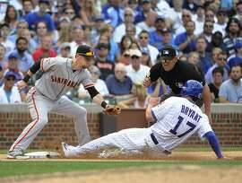 Chicago Cubs' Kris Bryant (17) is safe at third base on a wild pitch as San Francisco Giants third baseman Matt Duffy (5) makes a late tag during the seventh inning of a baseball game, Friday, Aug.  7, 2015, in Chicago. (AP Photo/David Banks)