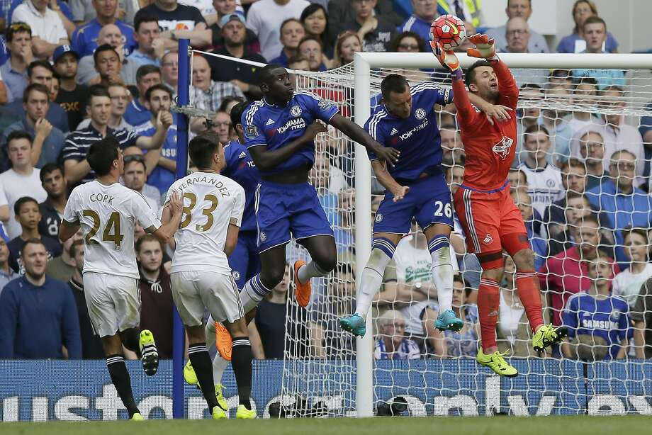 Swansea goalkeeper Lukasz Fabianski (right) corrals the ball against Chelsea's John Terry (26). Photo: Tim Ireland, Associated Press