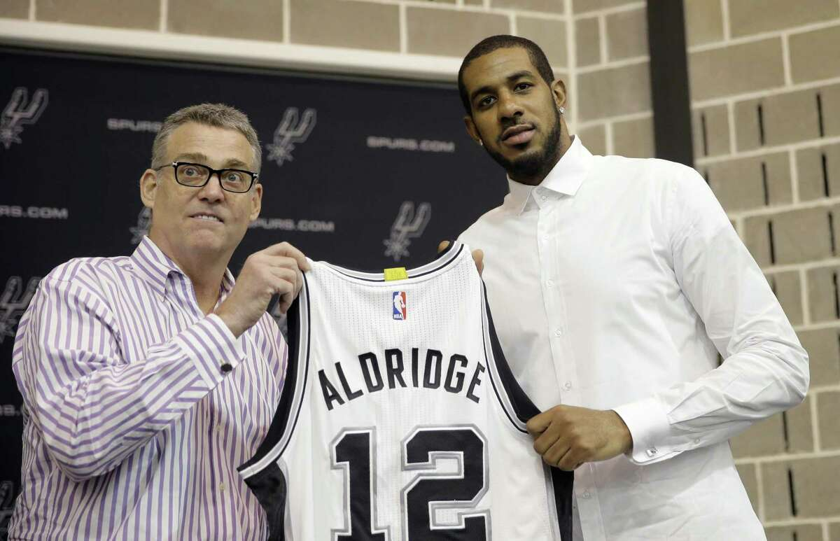 LaMarcus Aldridge, right, poses with San Antonio Spurs general manager R.C. Buford, left, and his new jersey during a news conference at the team's practice facility as he is formally introduced after he signed with the San Antonio Spurs NBA basketball team, Friday, July 10, 2015, in San Antonio.