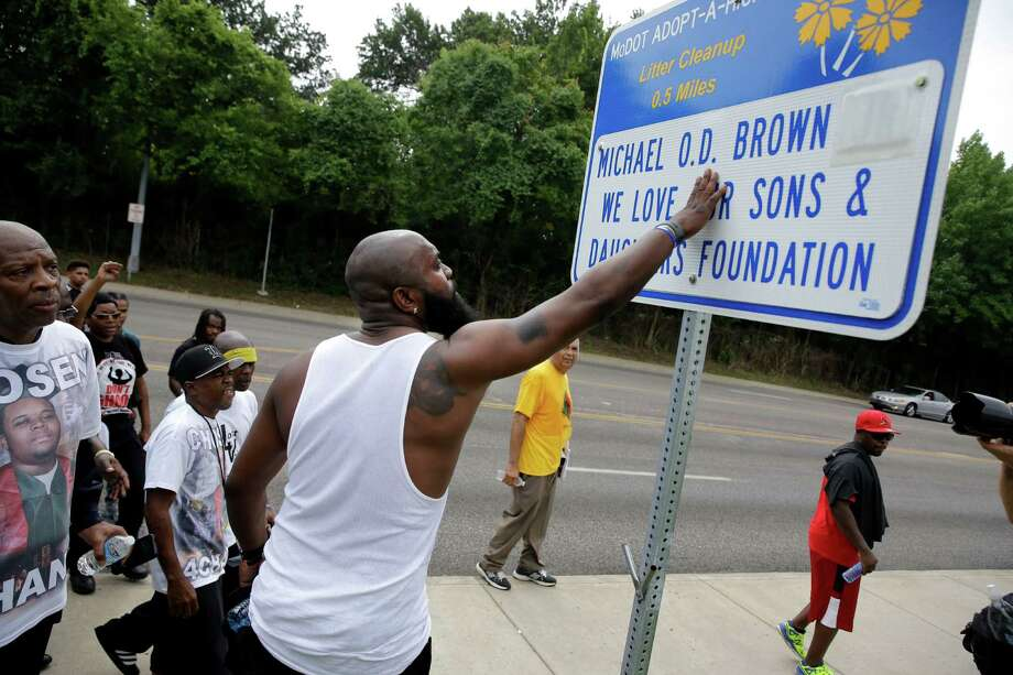 Michael Brown Sr. stops to touch an adopt-a-highway sign as he takes part in a parade in honor of his son, Michael Brown, Saturday, Aug. 8, 2015, in Jennings, Mo. Sunday will mark one year since Michael Brown was shot and killed by Ferguson police officer Darren Wilson. (AP Photo/Jeff Roberson) Photo: Jeff Roberson, STF / Associated Press / AP