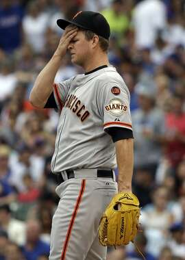 San Francisco Giants starter Matt Cain wipes his face after Chicago Cubs' Anthony Rizzo walked to first base during the first inning of a baseball game Saturday, Aug. 8, 2015, in Chicago. (AP Photo/Nam Y. Huh)