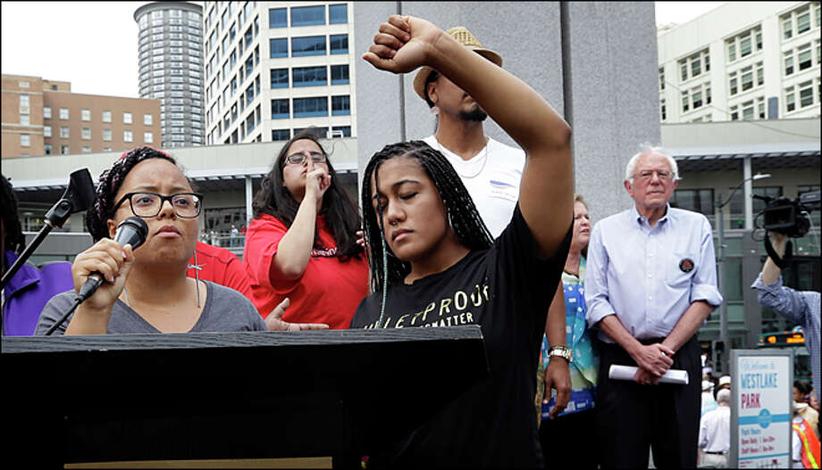 Marissa Johnson, left, speaks as Mara Jacqueline Willaford holds her fist overhead and Democratic presidential candidate Sen. Bernie Sanders, I-Vt., stands nearby as the two women take over the microphone at a rally Saturday, Aug. 8, 2015, in downtown Seattle. The women, co-founders of the Seattle chapter of Black Lives Matter, took over the microphone and refused to relinquish it. Sanders eventually left the stage without speaking and instead waded into the crowd to greet supporters. (AP Photo/Elaine Thompson) Photo: Elaine Thompson, AP/Elaine Thompson / AP