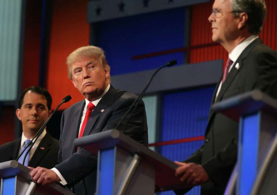 Republican presidential candidate Donald Trump looks toward Jeb Bush, right, as Scott Walker watches during the first Republican presidential debate at the Quicken Loans Arena Thursday, Aug. 6, 2015, in Cleveland. (AP Photo/Andrew Harnik) ORG XMIT: OHAH504 Photo: Andrew Harnik / AP