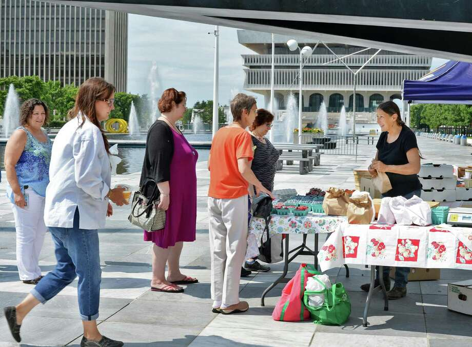 Betty Anne Paris, right, of Maynard Farms in Ulster Park sells her fruit under Ronald Bladen's 1972 sculpture The Cathedral Evening during a farmers market at the Empire State Plaza Wednesday July 15, 2015 in Albany, NY.  (John Carl D'Annibale / Times Union) Photo: John Carl D'Annibale / 00032594A