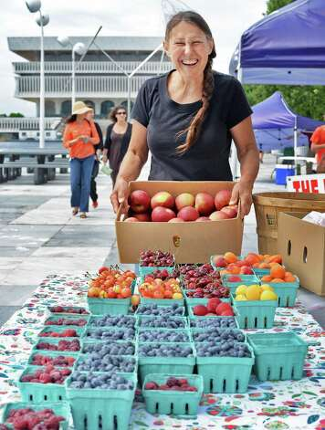 Betty Anne Paris of Maynard Farms in Ulster Park sets up her fruits during the farmers market at the Empire State Plaza Wednesday July 15, 2015 in Albany, NY.  (John Carl D'Annibale / Times Union) Photo: John Carl D'Annibale / 00032594A