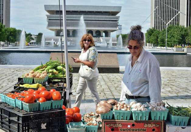 Shoppers check out fresh produce during the farmers market at the Empire State Plaza Wednesday July 15, 2015 in Albany, NY.  (John Carl D'Annibale / Times Union) Photo: John Carl D'Annibale / 00032594A