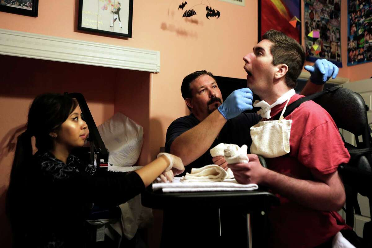 Nurse Valerie Agustin, left, encourages John Gibson, 26, as he attempts to hold his head up during a physical therapy session with Physical Therapist Spencer Goff, middle, in his San Diego home on Monday, July 20, 2015.