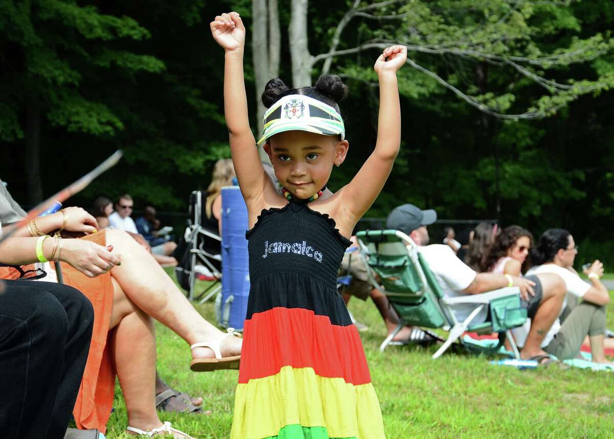 Three-year-old Zailyn Armenteros dances to reggae next to her Norwalk family during the fourth annual Reggae Festival at Ives Concert Park in Danbury, Conn., on Saturday, Aug. 8, 2015.