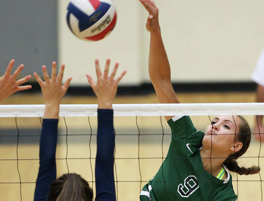 Reagan hitter Faith Squier slams from her corner over Claire Koskie as Reagan beats Johnson 3-0 at Littleton Gym on September 16, 2014. Photo: Tom Reel /San Antonio Express-News