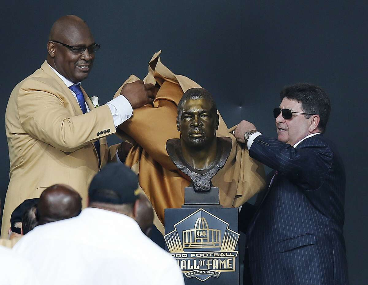 Former NFL player Charles Haley, left, unveils his bust with his presenter, former San Francisco 49ers owner Edward DeBartolo Jr., during an induction ceremony at the Pro Football Hall of Fame, Saturday, Aug. 8, 2015, in Canton, Ohio. (AP Photo/Tom E. Puskar)