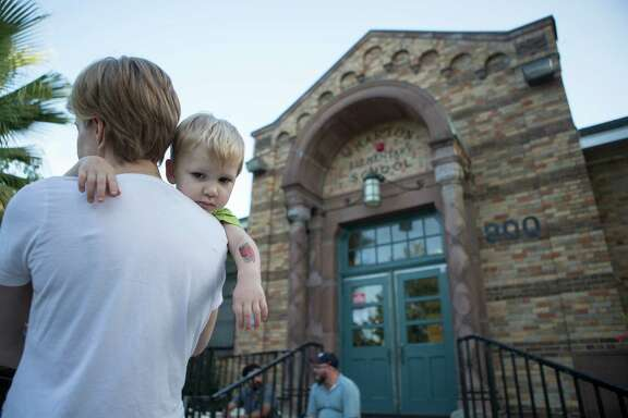 Ashley Dozier, with son Dima, 2, waits outside Wharton Elementary on Wednesday where she hopes to enroll her daughter.
