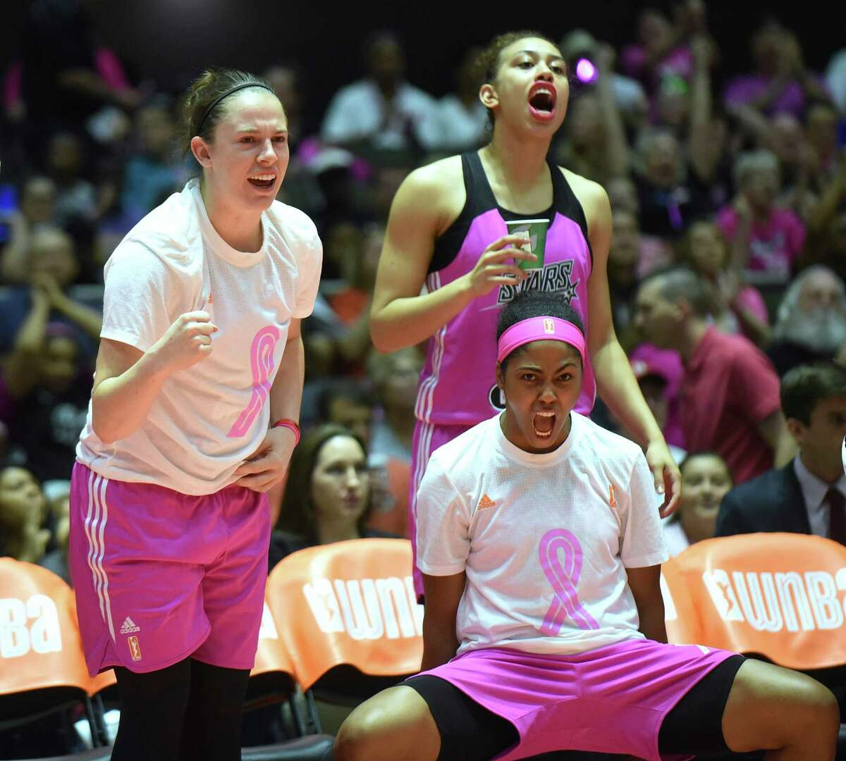 Samantha Logic, left, Dearica Hamby, and Sydney Colson, bottom, encourage their San Antonio Stars teammates during WNBA action against the Seattle Storm at Freeman Coliseum on Saturday, Aug. 8, 2015.