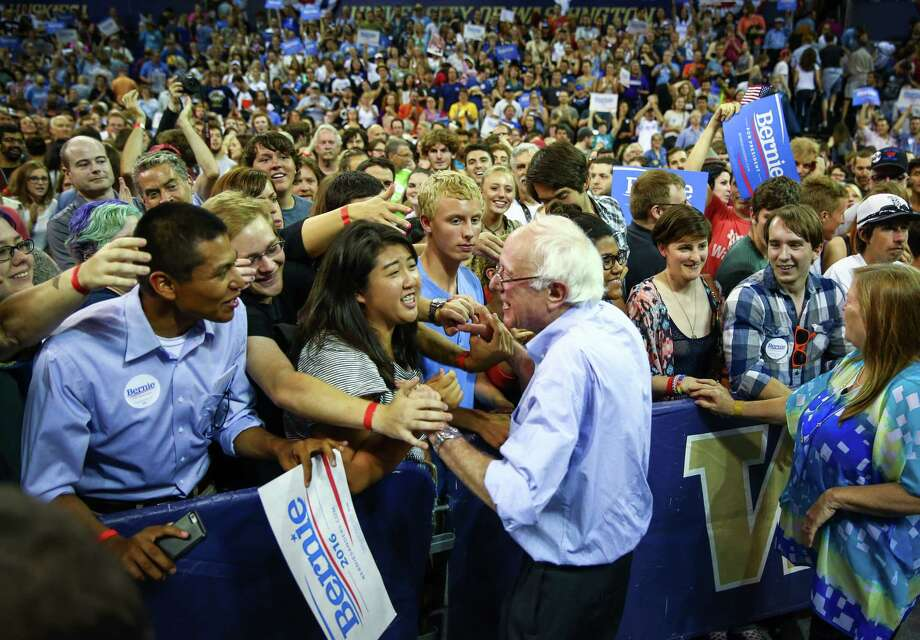 Bernie Sanders shakes hands with supporters during a rally at Hec Ed Pavilion that drew an estimated 15,000 people to the University of Washington. The rally filled the arena and left thousands outside. Earlier in the day Sanders participation in a rally at Westlake Park was cut short because protesters took over the microphone. Photographed on Saturday, August 8, 2015. Photo: JOSHUA TRUJILLO, SEATTLEPI.COM / SEATTLEPI.COM