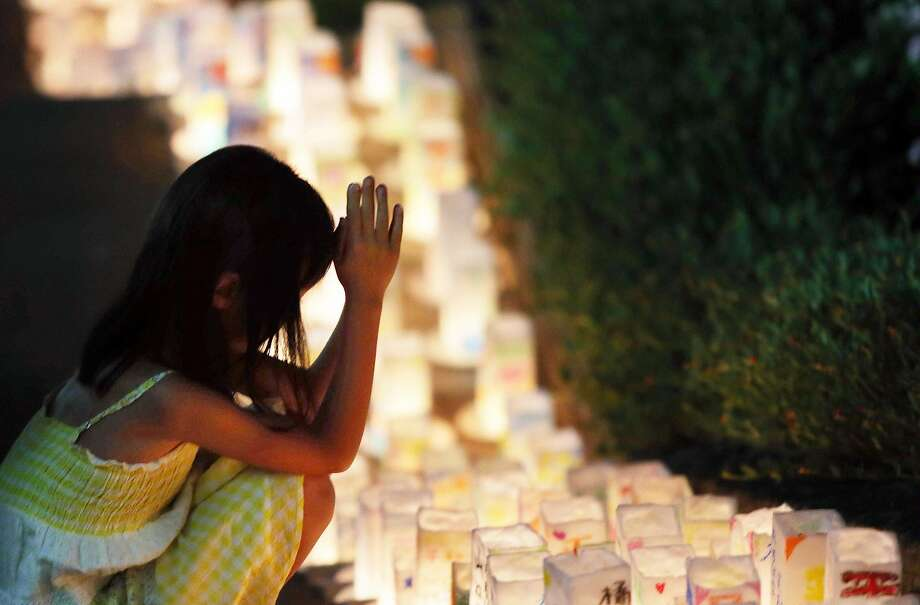 A girl offers a prayer for bomb victims before paper lanterns at the Peace Memorial Park in Nagasaki. Photo: Jiji Press, AFP / Getty Images