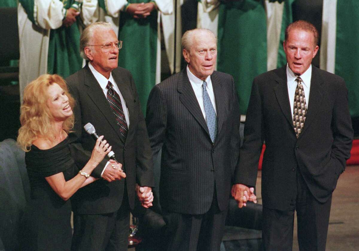 From left, Kathie Lee Gifford, the Rev. Billy Graham, former President Gerald R. Ford, and former New York Giants' Frank Gifford sing, 'America the Beautiful,' Thursday, Aug. 19, 1999, at DeVos Hall in Grand Rapids, Mich., during An Evening to Remember, A Tribute to the Honorable Gerald R. Ford, a 90-minute, revival-flavored tribute commemorating the 25th anniversary of the beginning of Ford's presidency.