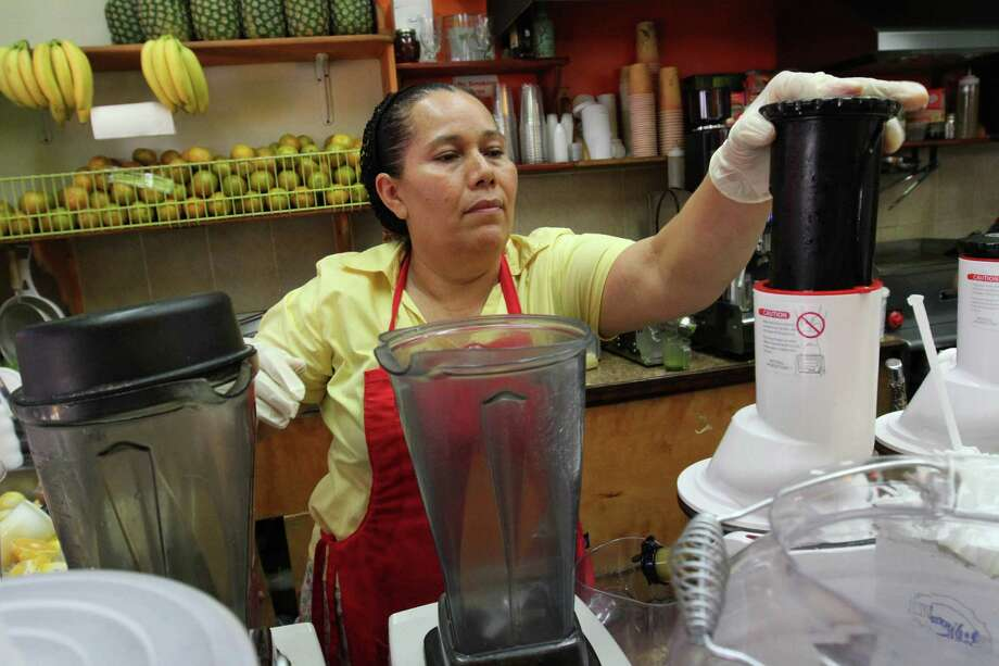 Celina Alvarez, 51, works at Jugueria de regreso al Eden, her shop in the Queens borough of New York. She says that at her first two jobs, she worked 12 hours per day, six days a week for a flat weekly wage of $350. That comes out to about $4.86 per hour. As a campaign to raise the minimum wage as high as $15 has rolled to victory in some cities, it has bumped up against a harsh reality: Plenty of scofflaw businesses don't pay the legal minimum now and probably won't pay the new, higher wages either. Photo: Tina Fineberg /Associated Press / FR73987 AP