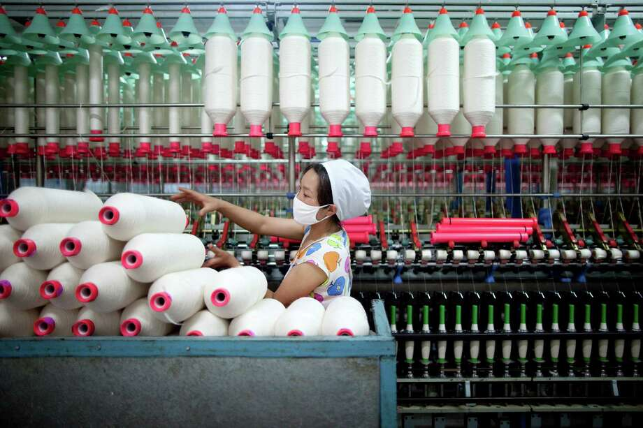 A worker manufactures cotton yarn at a factory in China. Companies are finding that it makes sense to shift operations such as yarn-spinning, which is heavily automated and doesn't require a lot of labor, to the United States. Several Chinese companies recently have invested in manufacturing facilites in the United States. Photo: Bloomberg News File Photo / 2011 Bloomberg Finance L.P.