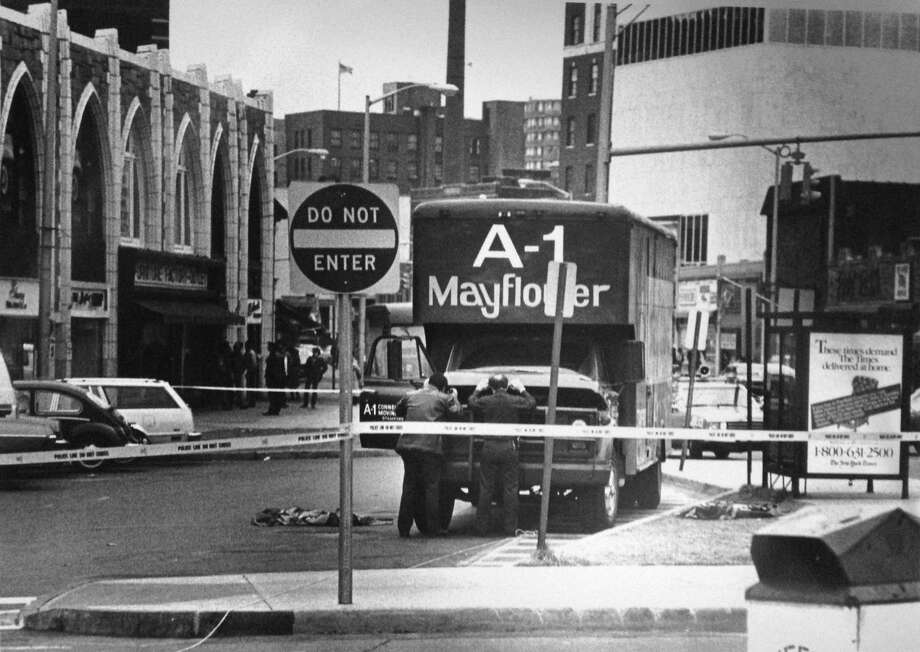 In this Advocate archive photo from Feb. 2, 1983, the Stamford police bomb squad checks out a parked moving truck on Bedford Street after a caller to a local radio station said that if it were moved it would explode. Officers Frank Pellegrino and Robert Harrington check under the hood after opening it very carefully. No bomb was found. The truck's owner later said he parked the truck in the loading zone for advertising purposes. Photo: Advocate File Photo / Hearst Connecticut Media / Stamford Advocate