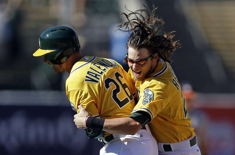 Danny Valencia is embraced by Josh Reddick after his hit capped the A's ninth-inning comeback against Houston. Photo: Ben Margot, Associated Press