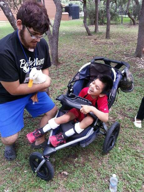Mark Andrade, 19, shows Daffy the Duck to Abel Garcia, 8, at the Eagles Flight Advocacy and Outreach summer program in Boerne. Photo: Courtesy Photo / Courtesy Photo