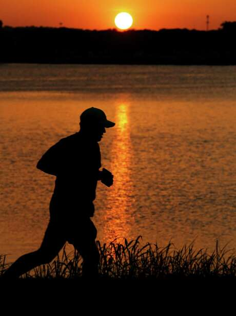 A jogger makes his way around Woodlawn Lake as the sun sets on Wednesday, July 30, 2015. Recent high temperatures reaching nearly triple digits have made work and recreation barely manageable during the day. But as the temperatures start to cool down, people resume their daily activities such as running around the lake. Chances for precipitation returns toward the weekend to offer some respite from the summer heat. (Kin Man Hui/San Antonio Express-News) Photo: Kin Man Hui, Staff / San Antonio Express-News / ©2015 San Antonio Express-News