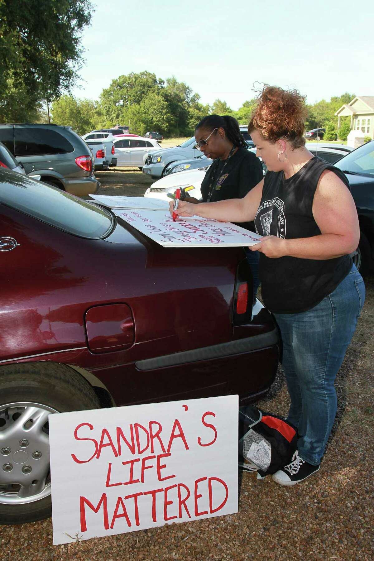 Gizelle Tolbert, left, and Shere Dore make signs for a rally Sunday at the Waller County Jail, where Sandra Bland died in custody last month after being arrested during a traffic stop.