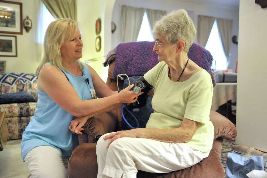 Kathleen Foti, left, an R.N. and a nurse care manager with Landmark Health, takes the blood pressure of Rebecca Behrendt at Behrendt's home on Wednesday, July 8, 2015, in Schenectady, N.Y.      (Paul Buckowski / Times Union) Photo: PAUL BUCKOWSKI / 00032526A