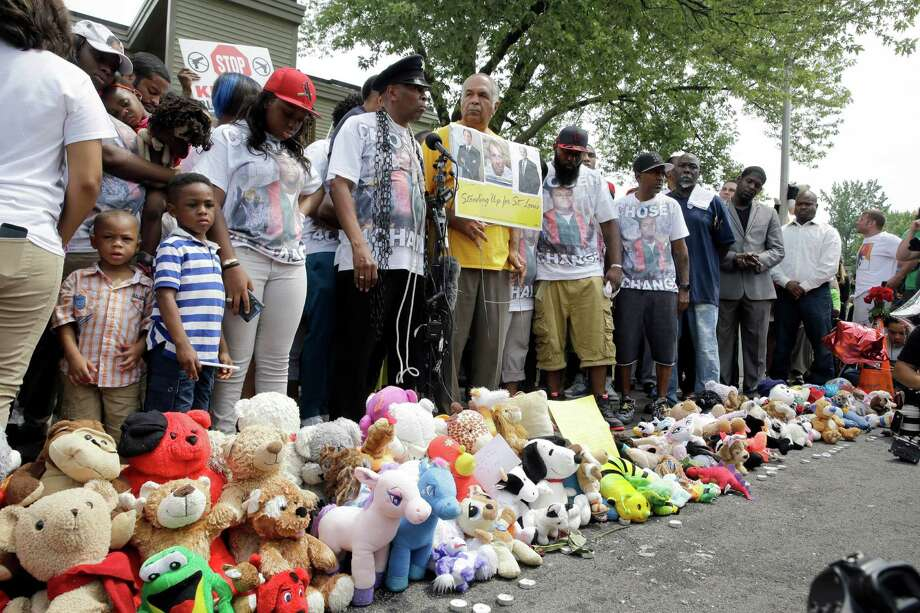 Family, friends and supporters pause for a moment of silence at a memorial to Michael Brown, Sunday, Aug. 9, 2015, in Ferguson, Mo. Sunday marks one year since Michael Brown was shot and killed by Ferguson police officer Darren Wilson. (AP Photo/Jeff Roberson) ORG XMIT: MOJR105 Photo: Jeff Roberson / AP