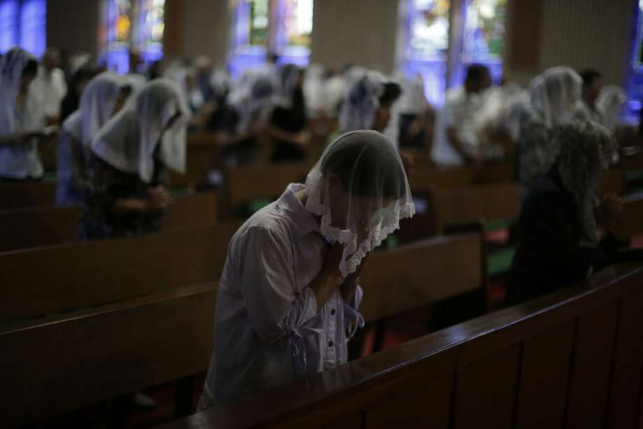 Catholics offer prayers at an early morning mass to pay respect to the victims of the atomic bombing at the Urakami Cathedral in Nagasaki, southern Japan Sunday, Aug. 9, 2015. Seventy years ago, a U.S.-dropped atomic bomb detonated about 500 meters (1,500 feet) from the church, killing two priests who were hearing confessions and about 30 others inside. The more than 70,000 who died in Nagasaki in the Aug. 9, 1945, bombing included 8,500 of the cathedral's 12,000 parishioners, decimating the largest Christian community in Japan.  Photo: Eugene Hoshiko, Associated Press