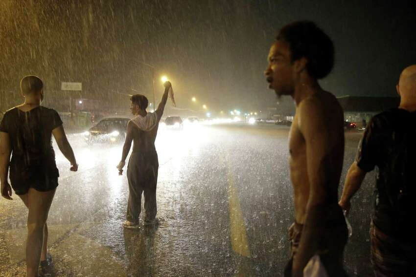 Protesters march in the rain, Sunday, Aug. 9, 2015, in Ferguson, Mo. Sunday marks one year since Michael Brown was shot and killed by Ferguson police officer Darren Wilson.