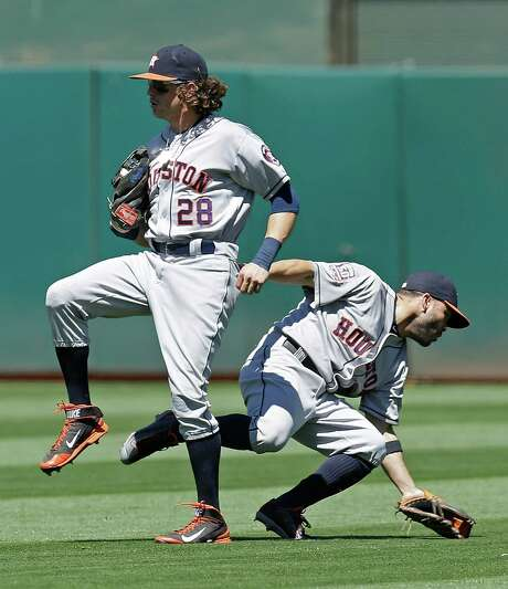 Astros right fielder Colby Rasmus (28) catches a popup by the A's Brett Lawrie in the fifth inning, with Jose Altuve narrowly avoiding a collision with Rasmus in short right field. Photo: Ben Margot, STF / AP
