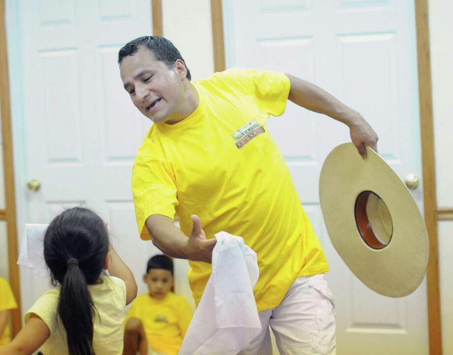 At top, Luis Trejo teaches dance student, Camila Lopez, 6, the Marinera Norteno, a Peruvian dance, in the dance studio he runs with his wife in Stamford, Conn., Friday, July 24, 2015. Photo: Bob Luckey Jr. / Hearst Connecticut Media / Greenwich Time
