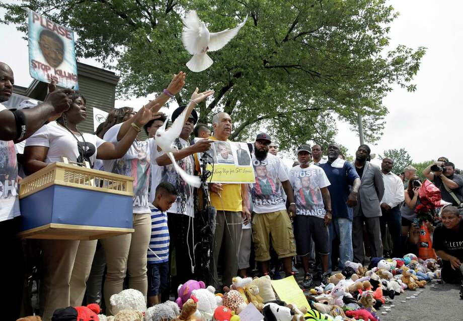 Doves are released at the end of a period of silence for Michael Brown in Ferguson, Mo. The 4½ minutes of silence represented the 4½ hours Brown lay in the street after he was killed a year ago by a police officer. Photo: Jeff Roberson / Associated Press / AP