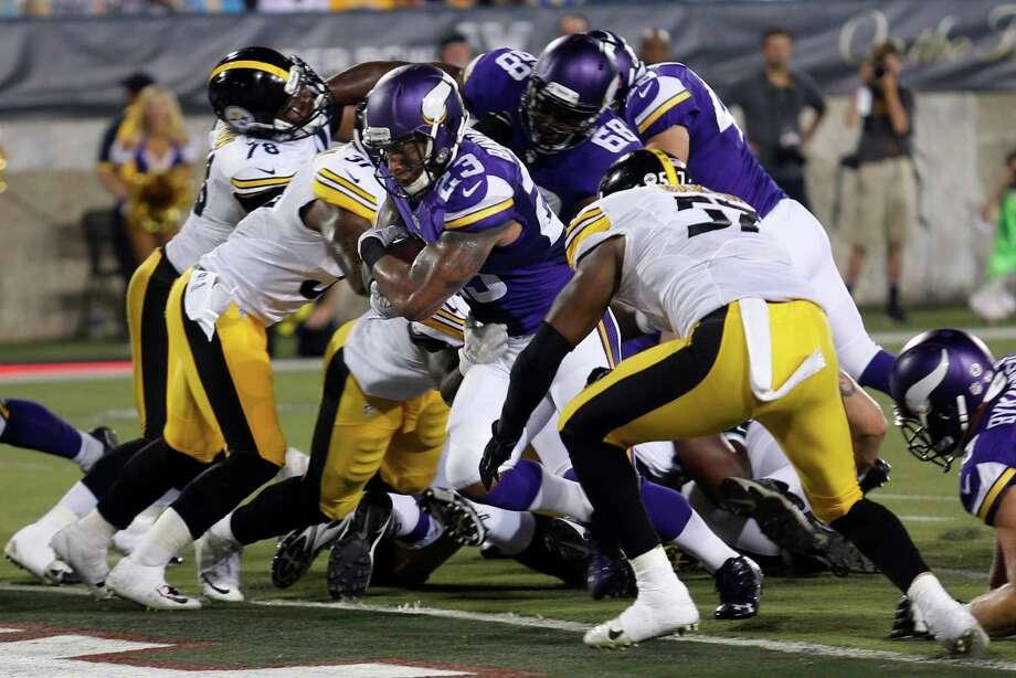 Minnesota Vikings running back Joe Banyard (23) rushes for a touchdown between Pittsburgh Steelers defenders  during the second half of an NFL preseason football game in Canton, Ohio,  Sunday, Aug. 9, 2015. (AP Photo/Tom E. Puskar) ORG XMIT: OHGP121 Photo: Tom E. Puskar / FR60050